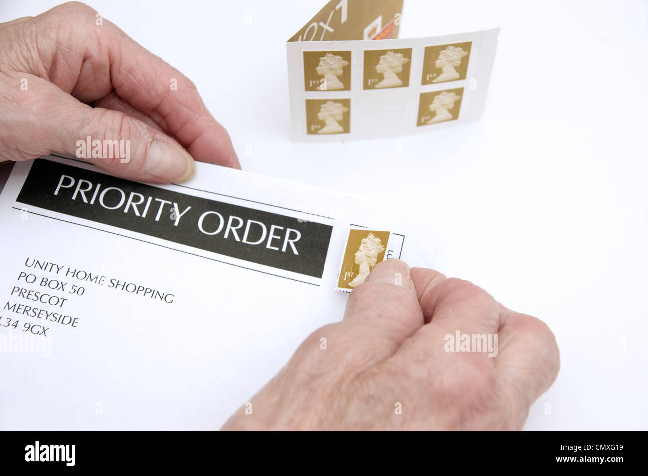 Elderly woman putting a 1st first class stamp on an envelope ready for posting (price increases 30th April 2012 - Stock Image