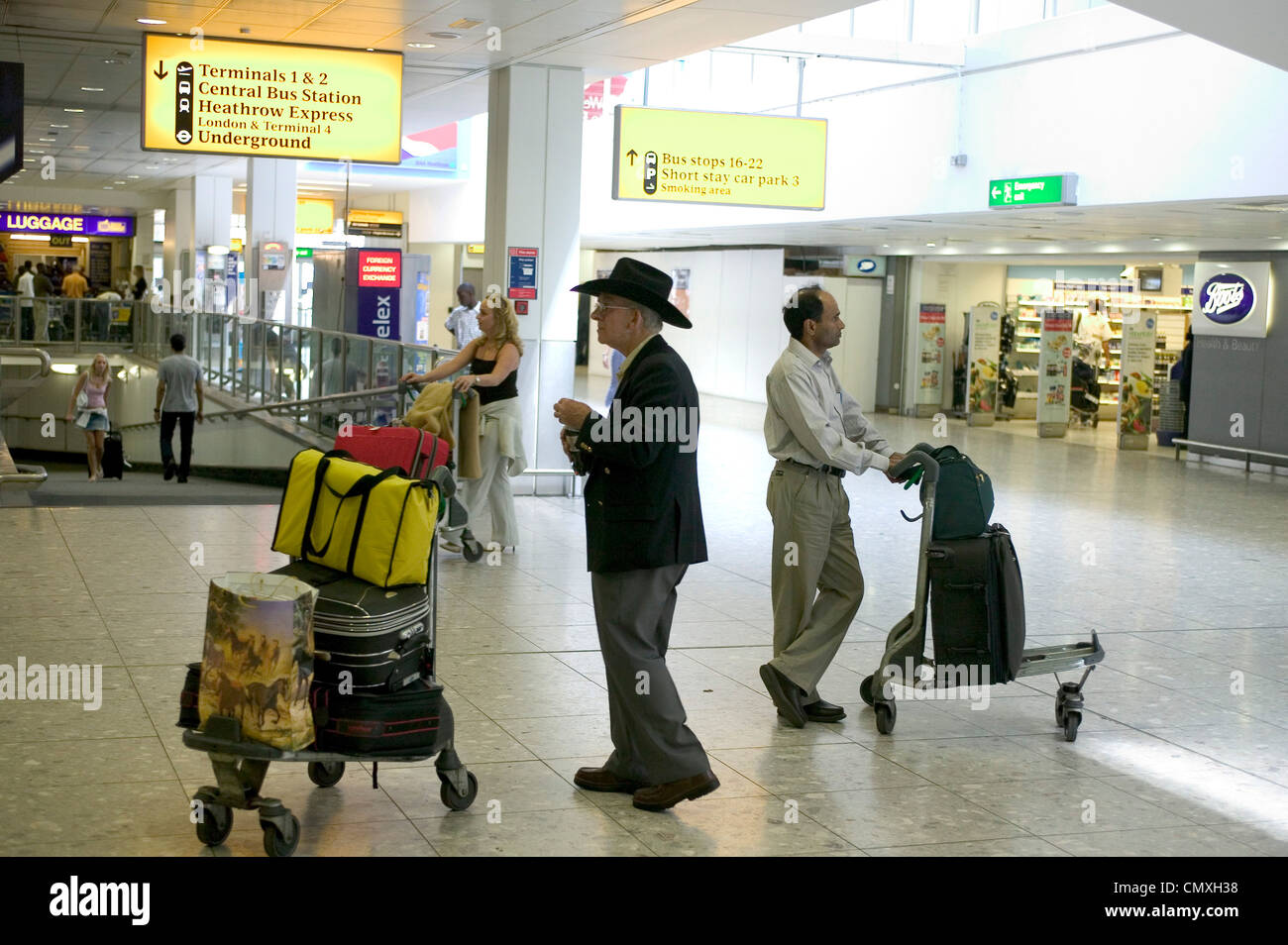 Passenger with baggage trolley at the arrivals area heathrow airport - Stock Image