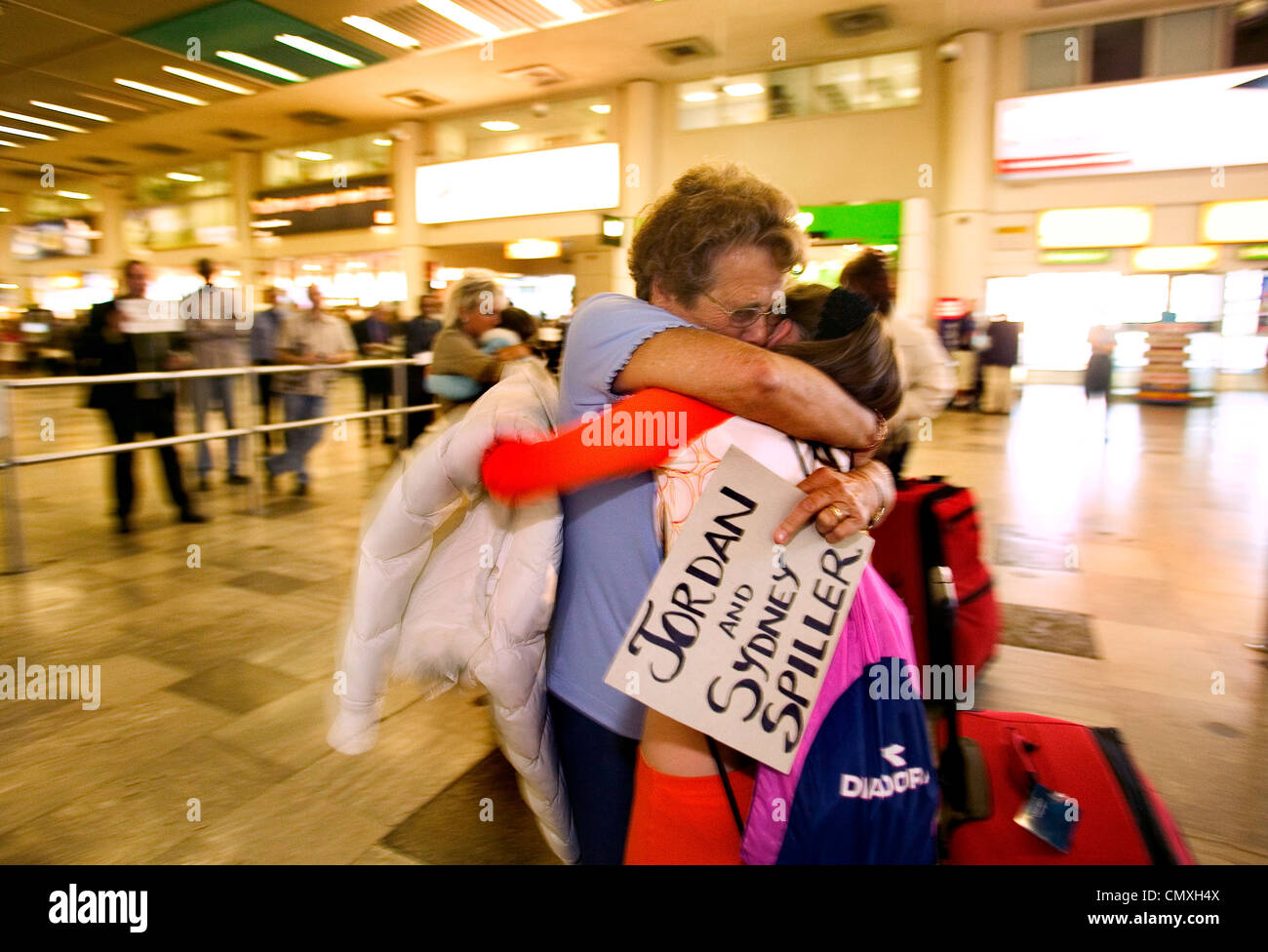 family reunited in the arrival area at Heathrow airport - Stock Image