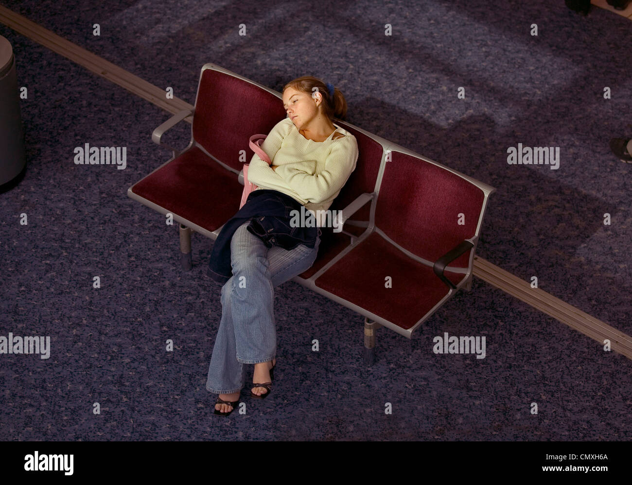 Woman passenger asleep in the seating area of departure lounge at Heathrow airport - Stock Image
