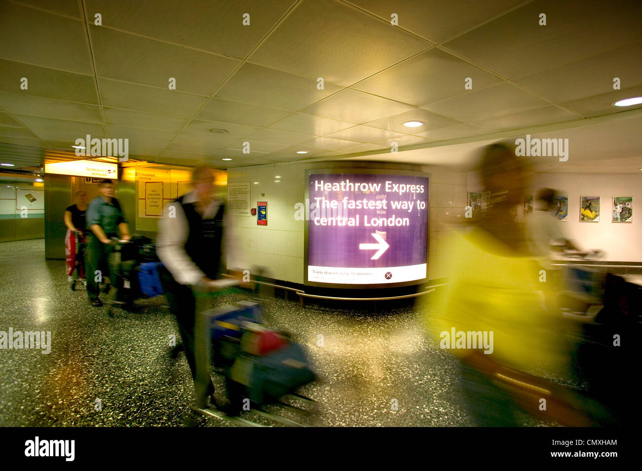Passengers arriving at Heathrow airport in the arrival area - Stock Image
