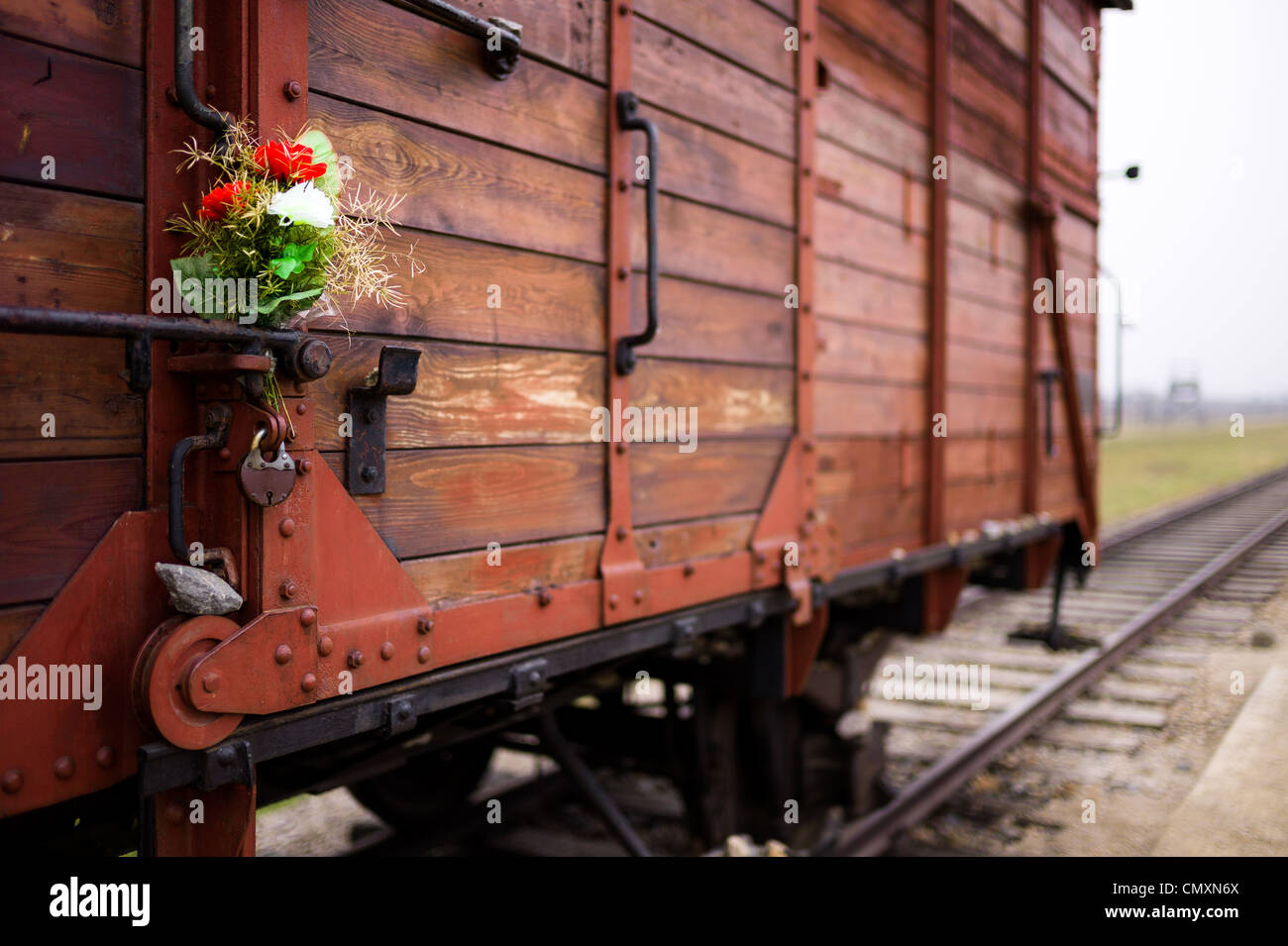 Memorial flowers placed on a prisoner transport carriage at Auschwitz II, Birkenau, Poland Stock Photo