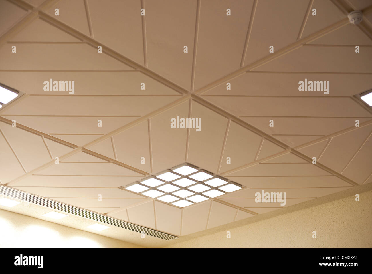 Strip lights ceiling stock photos strip lights ceiling stock beige and white ceiling tile patterns in an office stock image mozeypictures Gallery