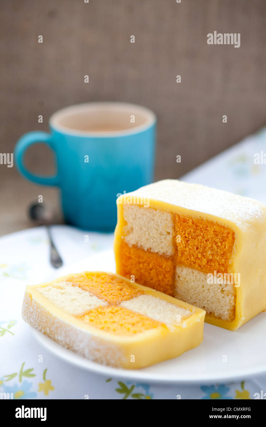 Homemade Battenburg cake on a floral sheet against hessian material with a spoon and mug or cup of tea. Picnic look - Stock Image