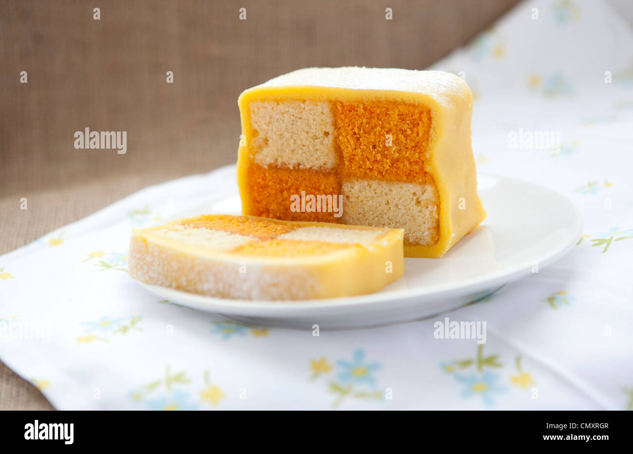 Homemade Battenburg cake on a floral sheet against hessian material. Picnic look inside. - Stock Image