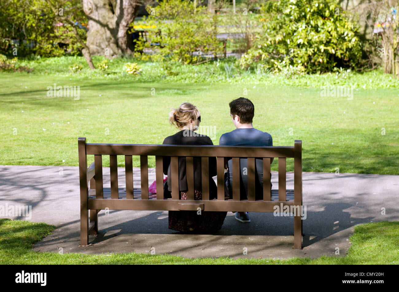 A Young Couple Sitting On A Park Bench Rear View Abbey Gardens