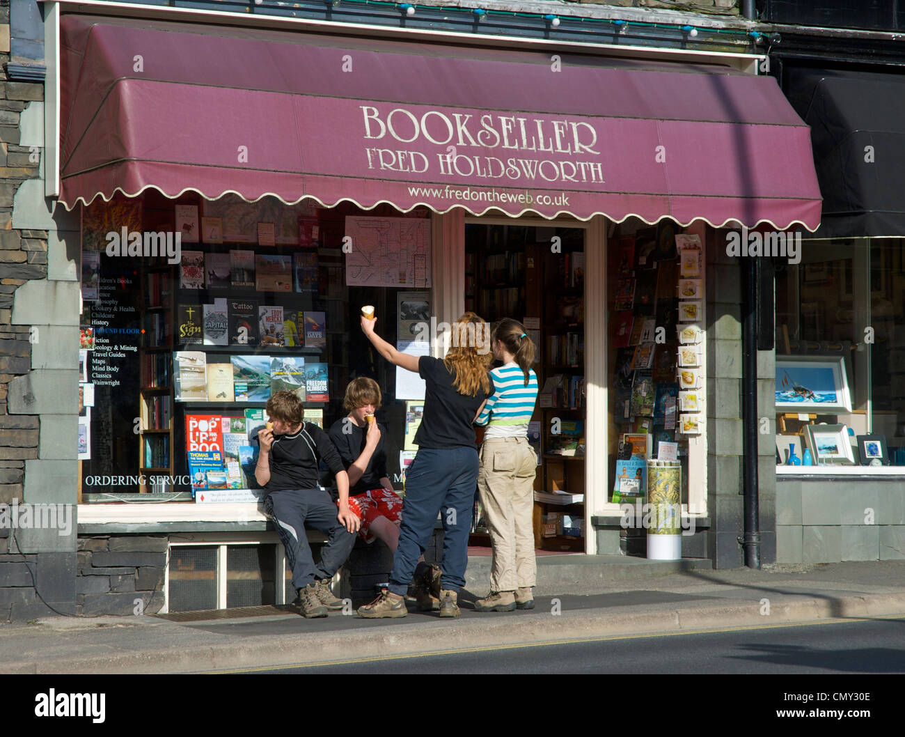 Four young people outside a bookshop, eating ice creams, in the town of Ambleside, Cumbria, England UK - Stock Image