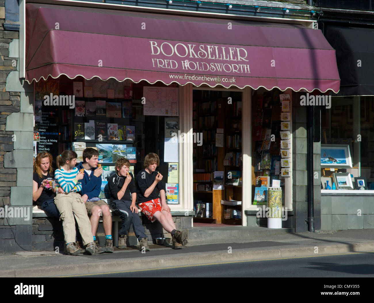 Five young people sitting outside a bookshop, eating ice creams, in the town of Ambleside, Cumbria, England UK - Stock Image