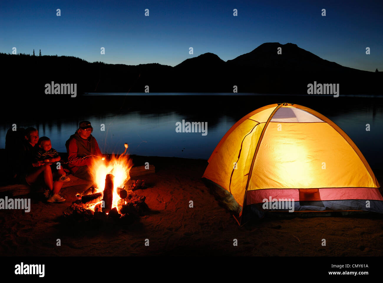 Camping Family Roasting Marshmallows Over A Campfire With Glowing Tent And Sparks Lake At Dusk South Sister Mountain Cascade Mountains Oregon