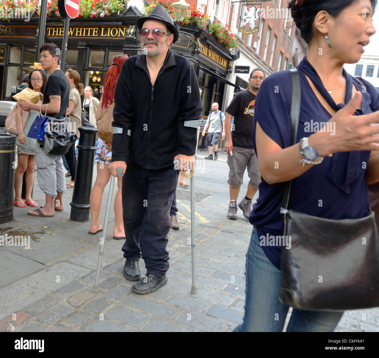 London, England. Disabled man on crutches - Stock Image