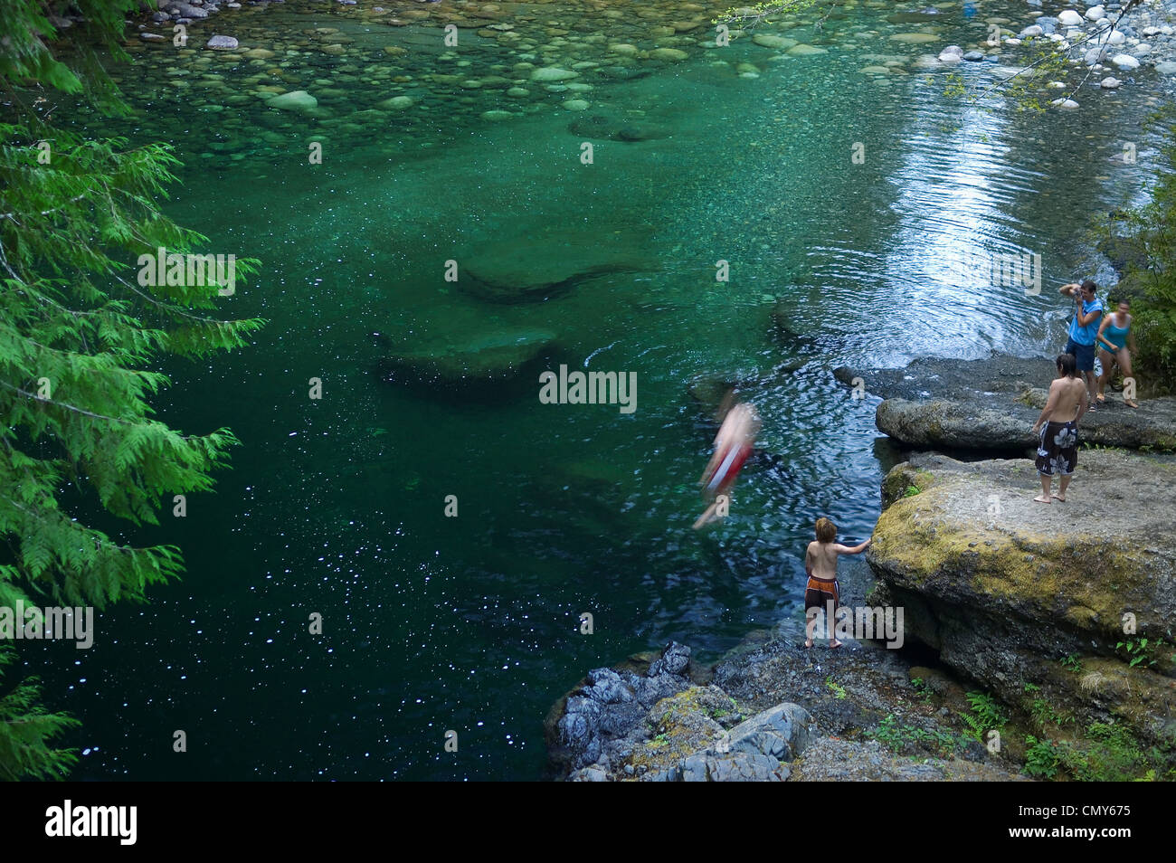 Boys jumping into swimming hole on Englishman river Vancouver Island British Columbia Canada - Stock Image