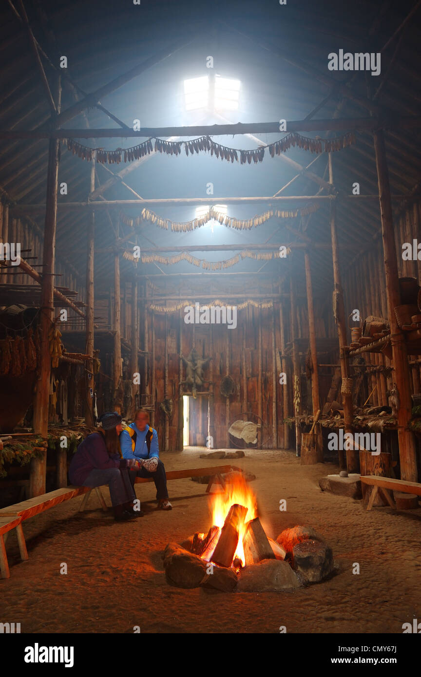 Replica of an Iroquois Native American Indian Longhouse with campfire fire smoke Crawford Lake Ontario Canada - Stock Image