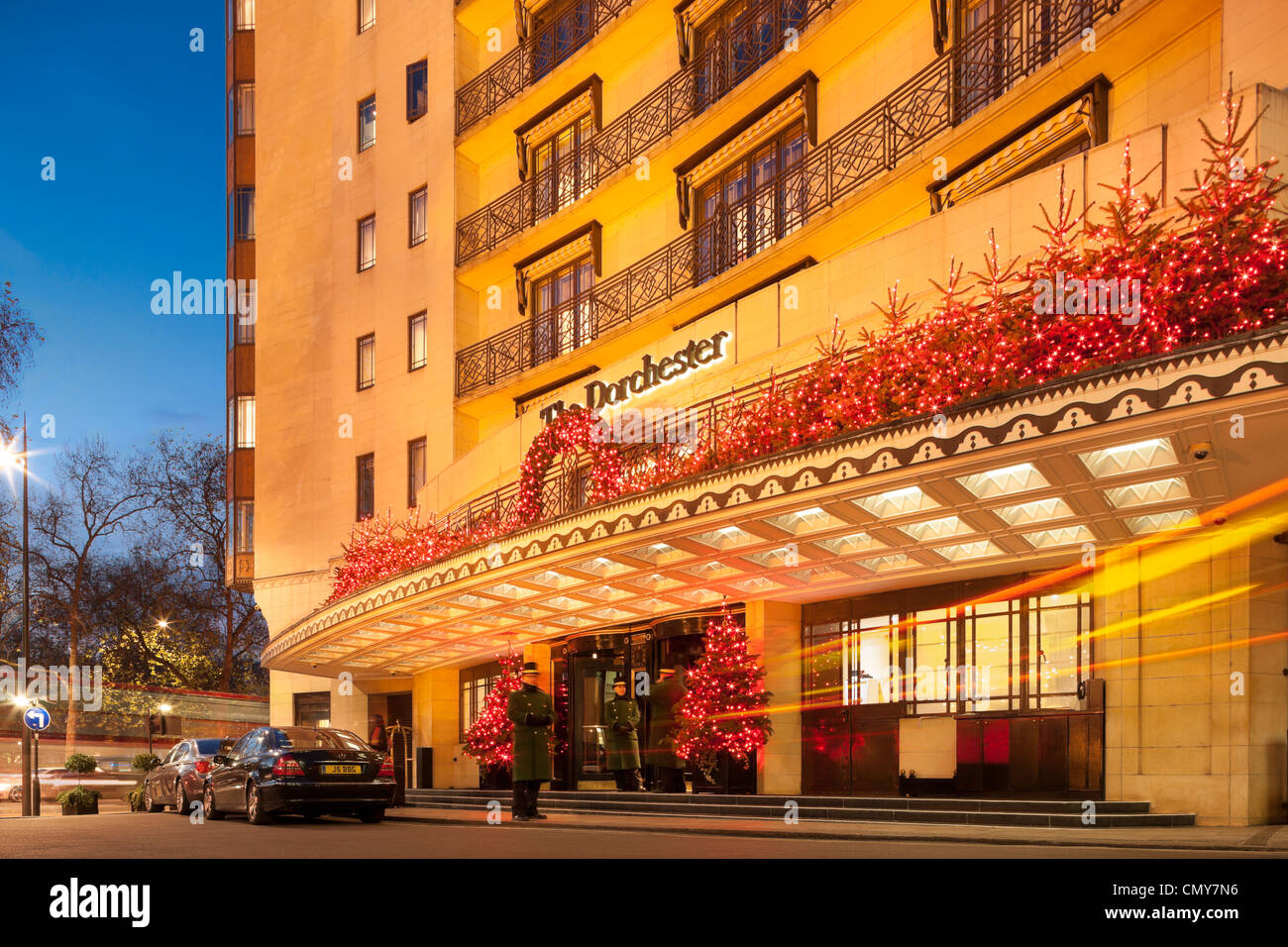 The Dorchester Hotel Park Lane London with Christmas decorations at dusk. Five star luxury hotel, entrance, doorman - Stock Image