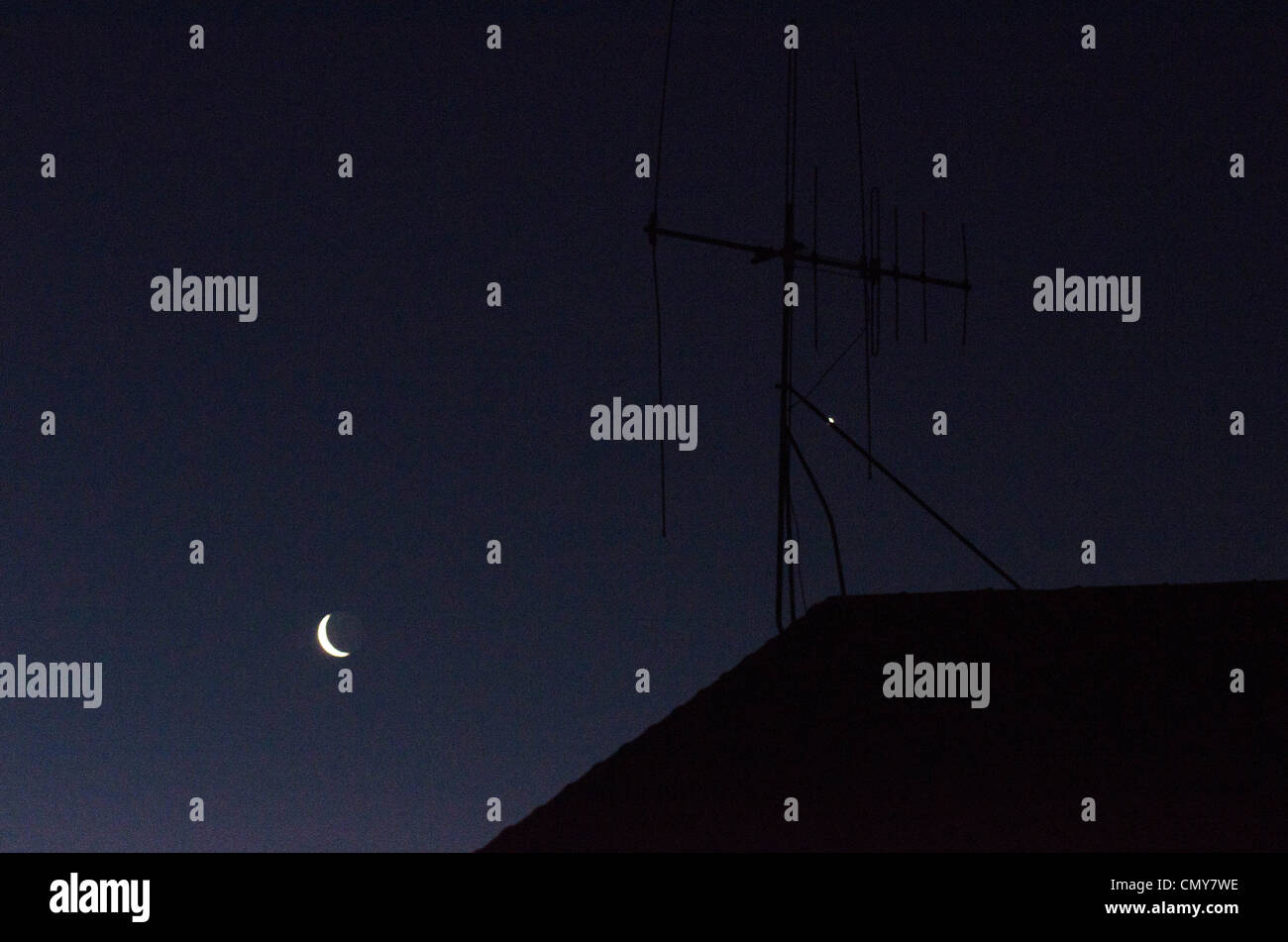A Night Sky with the Moon and TV aerial antenna on house roof. - Stock Image