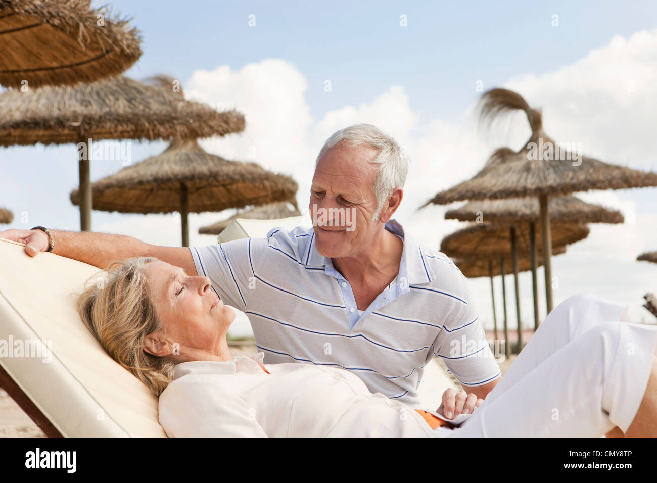 Spain, Mallorca, Senior man looking at woman resting on deck chair at beach - Stock Image