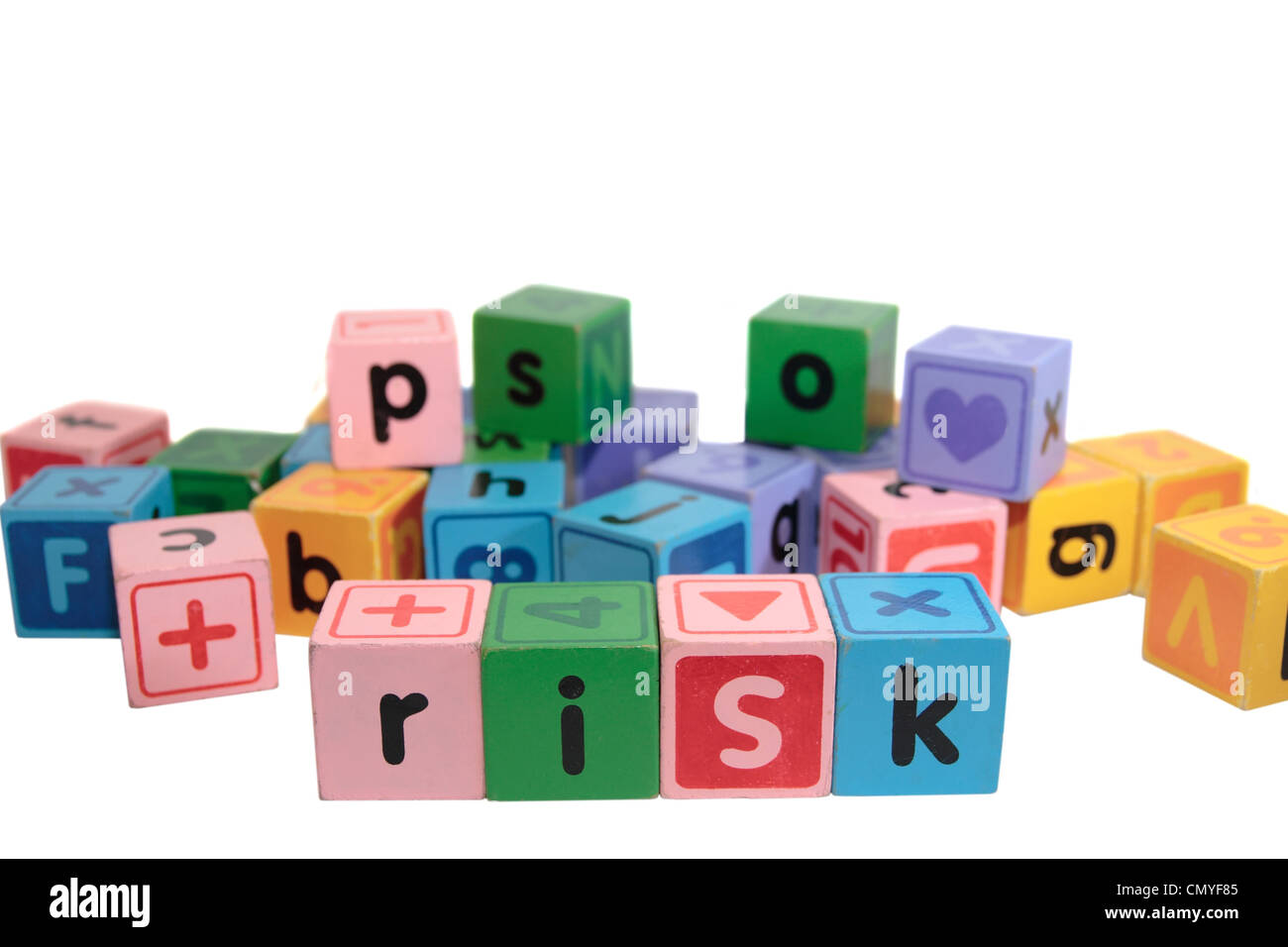 assorted childrens toy letter building blocks against a white background that spell risk - Stock Image