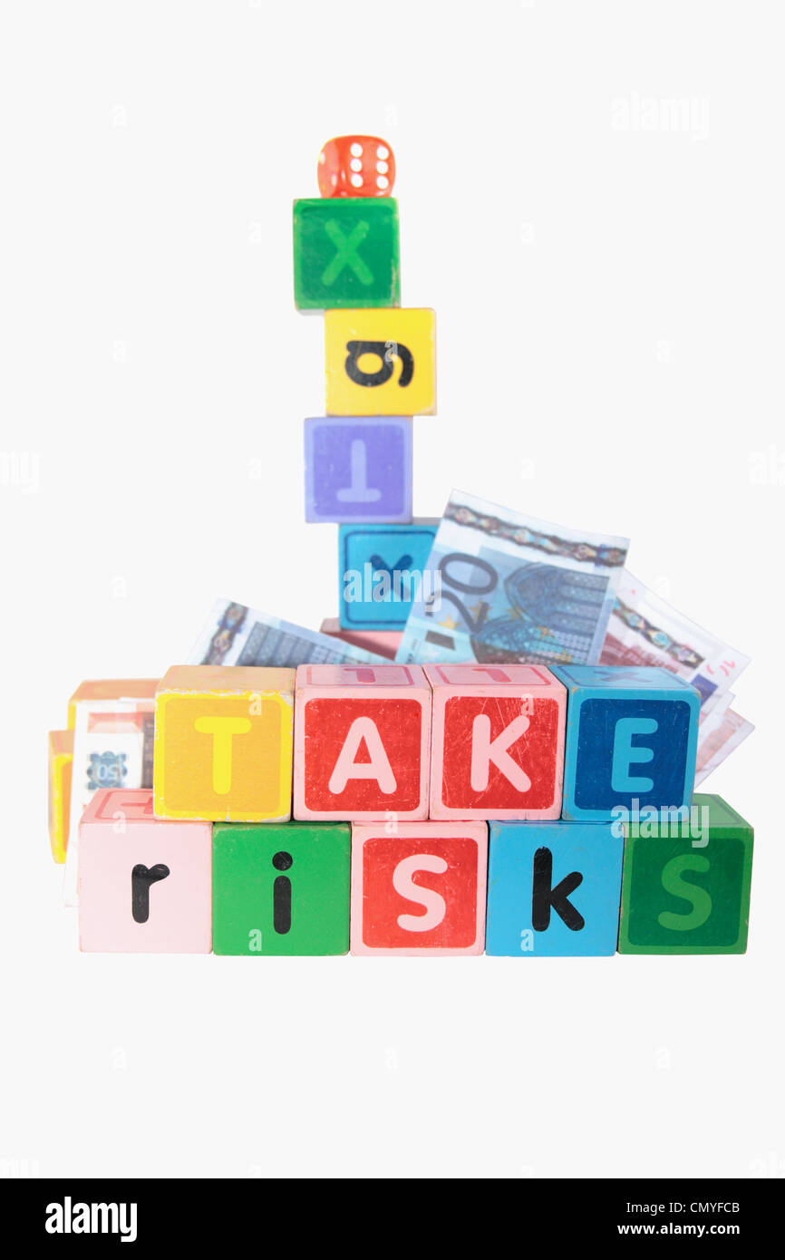 assorted childrens toy letter building blocks against a white background that spell take risks - Stock Image