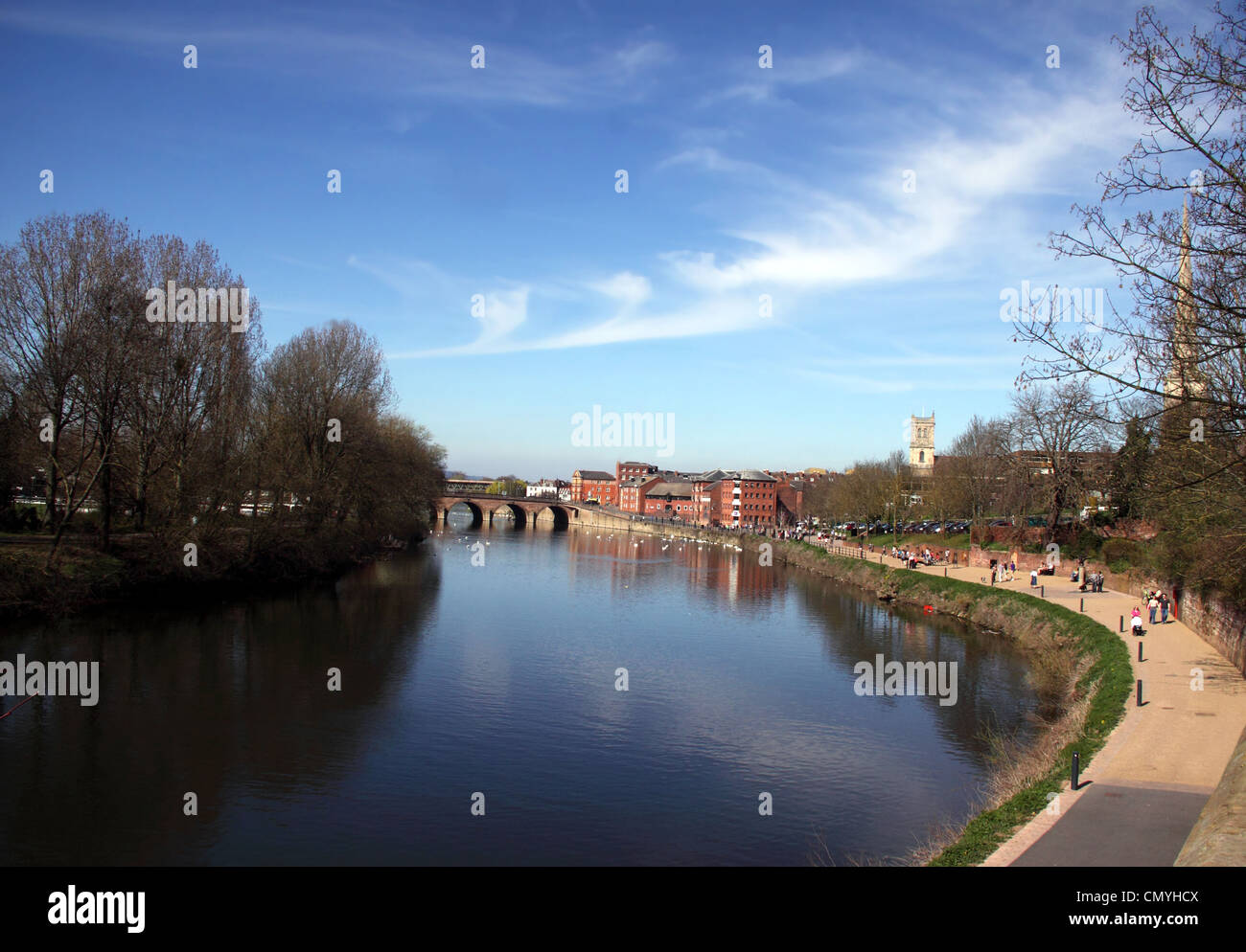 View along the River Severn at Worcester to Worcester Bridge. People walking along the footpath at the side. Blue - Stock Image