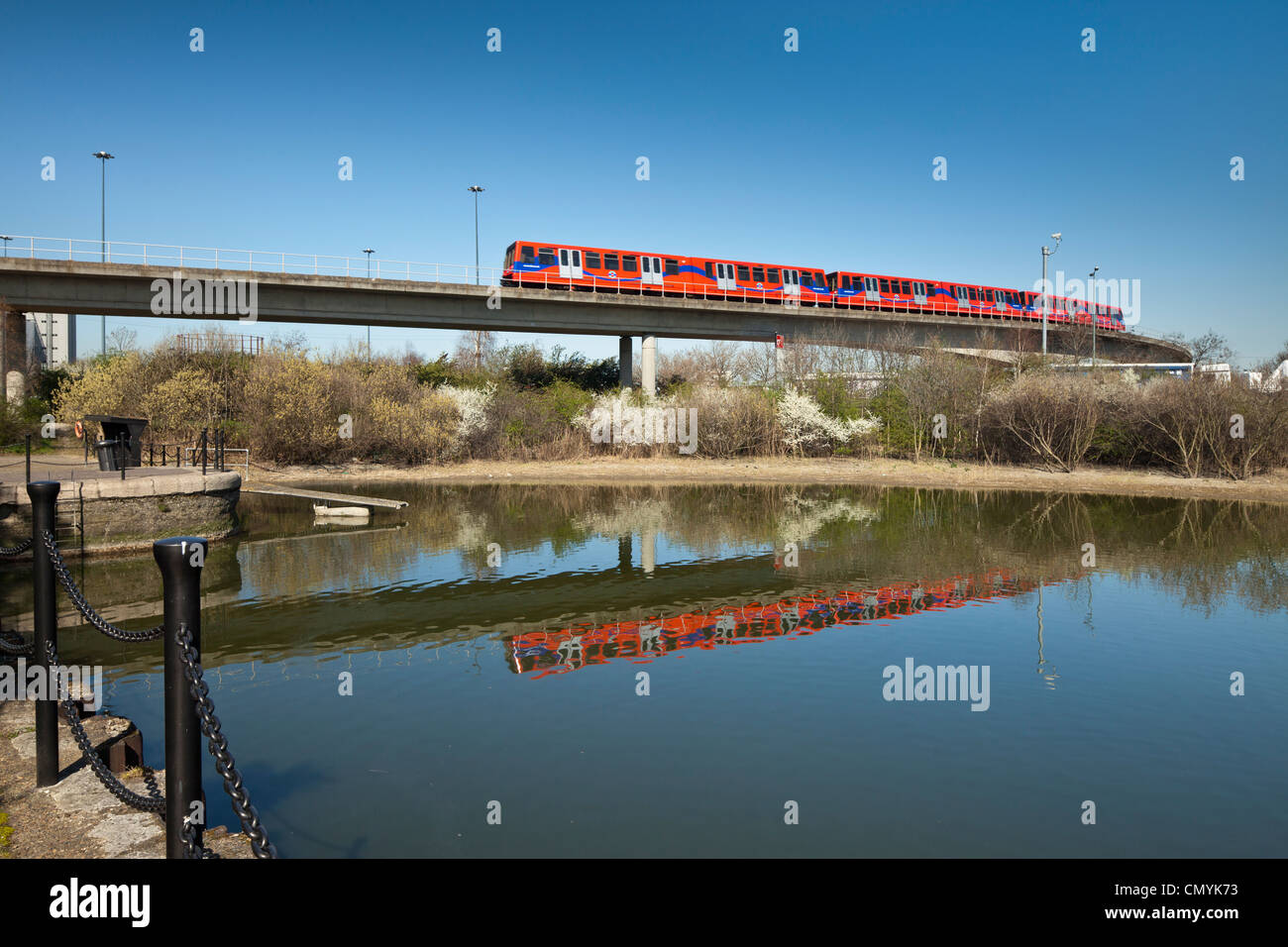 Docklands Light railway train reflected in East India Dock basin. - Stock Image