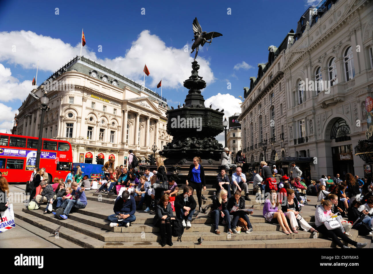 United Kingdom, London, Piccadilly Circus, crowd sitting at the foot of the statue of Eros - Stock Image