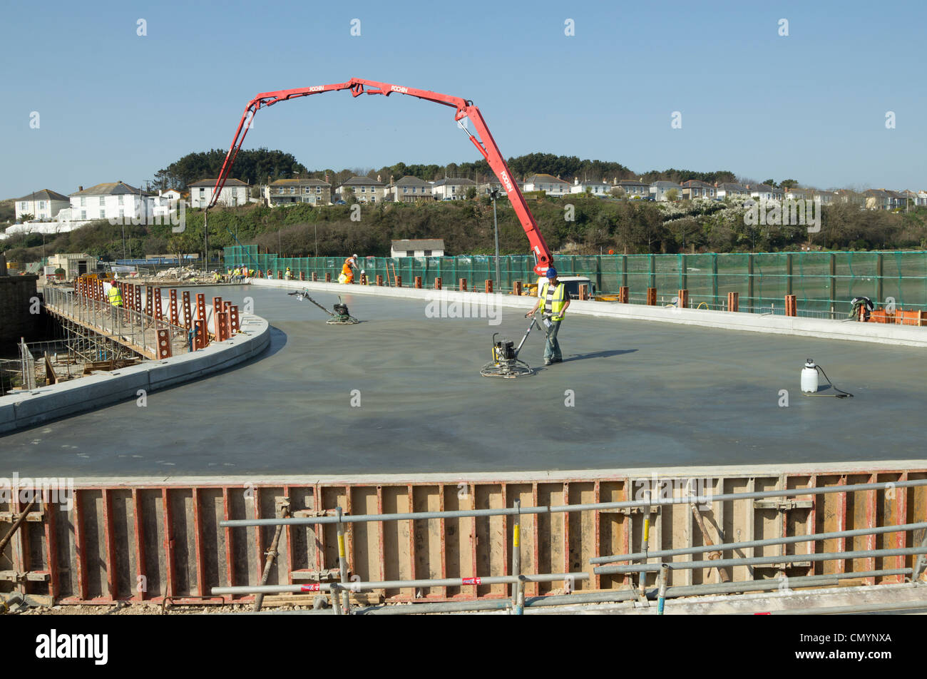 Smoothing the concrete during the concrete pour for the deck of the new bridge over Copperhouse Pool in Hayle, Cornwall UK. Stock Photo
