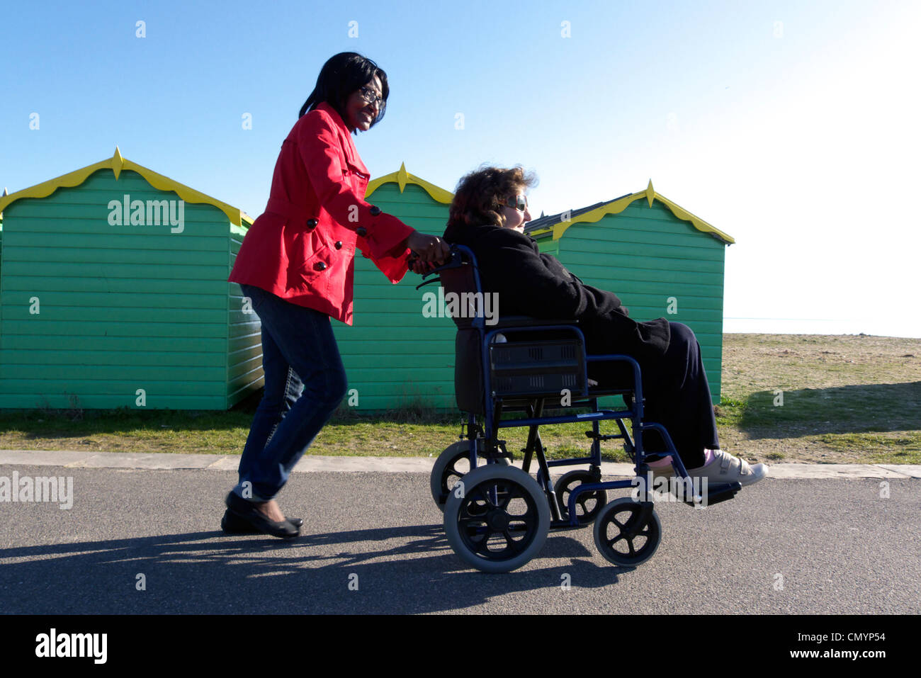 united kingdom west sussex littlehampton an elderly woman being wheeled in a wheelchair past beach huts - Stock Image