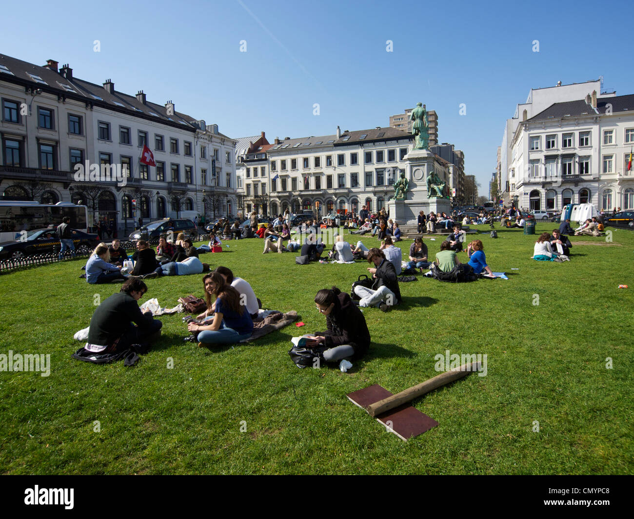 Many people enjoying the sun during their lunch break on the grass of the Place du Luxembourg in Brussels, Belgium Stock Photo