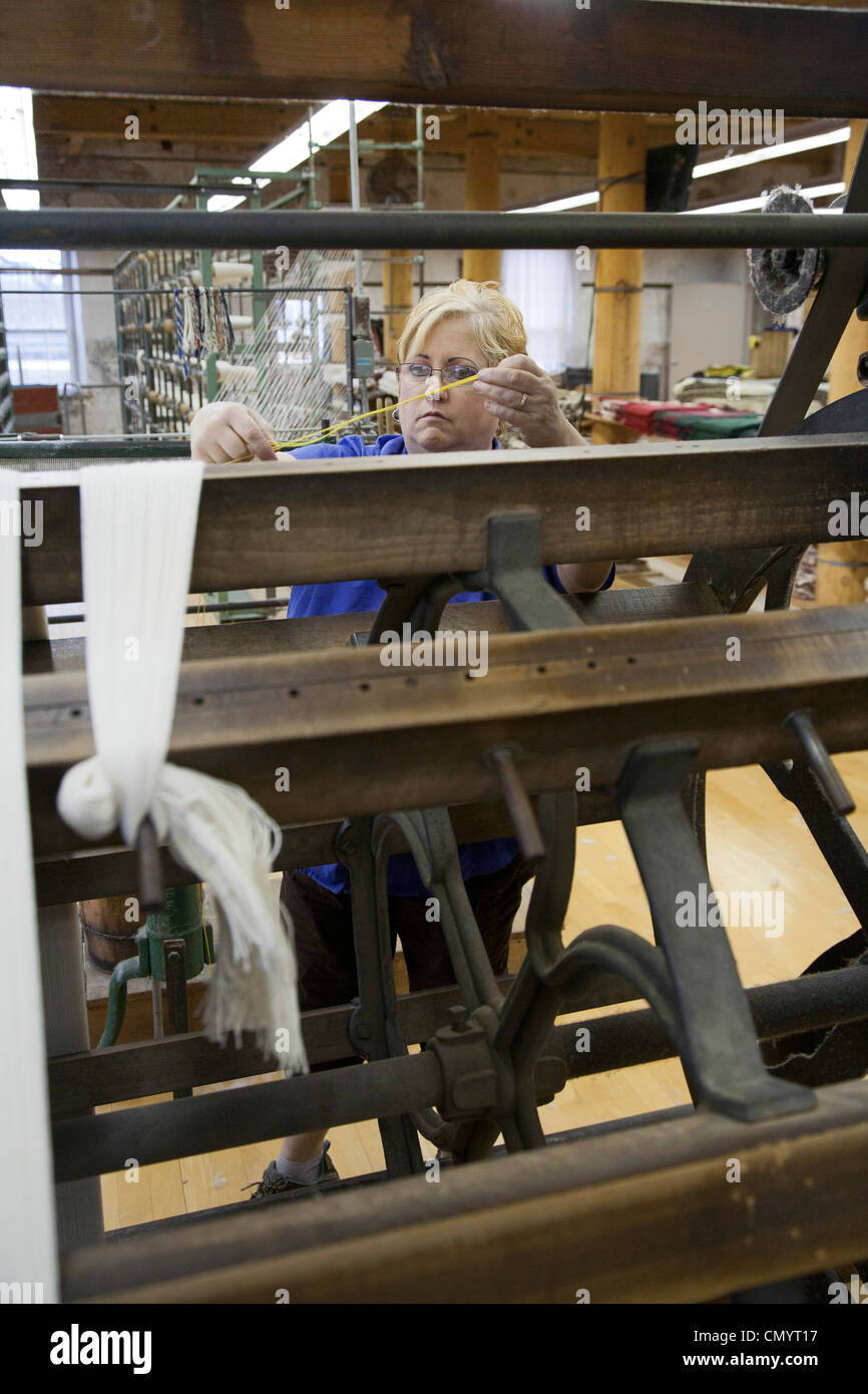 A worker runs a warping creel at the Amana Woolen Mill. - Stock Image