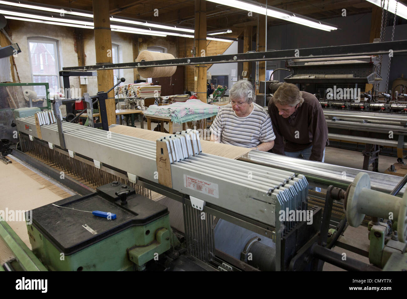Workers operate a loom at the historic Amana Wollen Mill - Stock Image