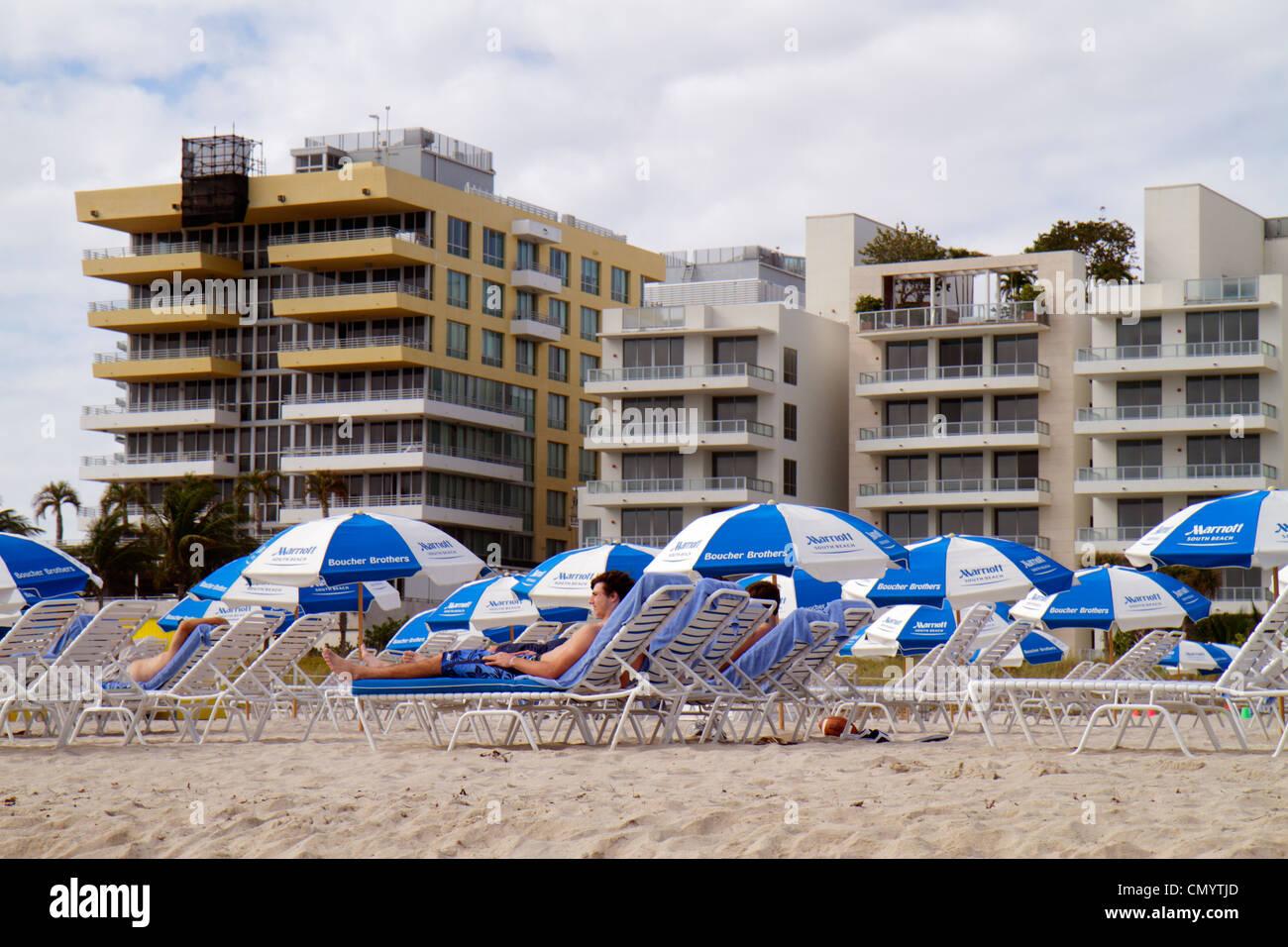 Miami Beach Florida rental lounge chairs condominium building man sunbathing public beach Stock Photo