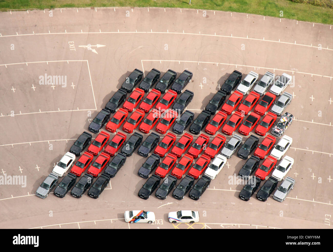 Aerial view of 66 M3 Series BMW Cars arranged into an M Shape to emulate an image taken in Germany decades ago. - Stock Image