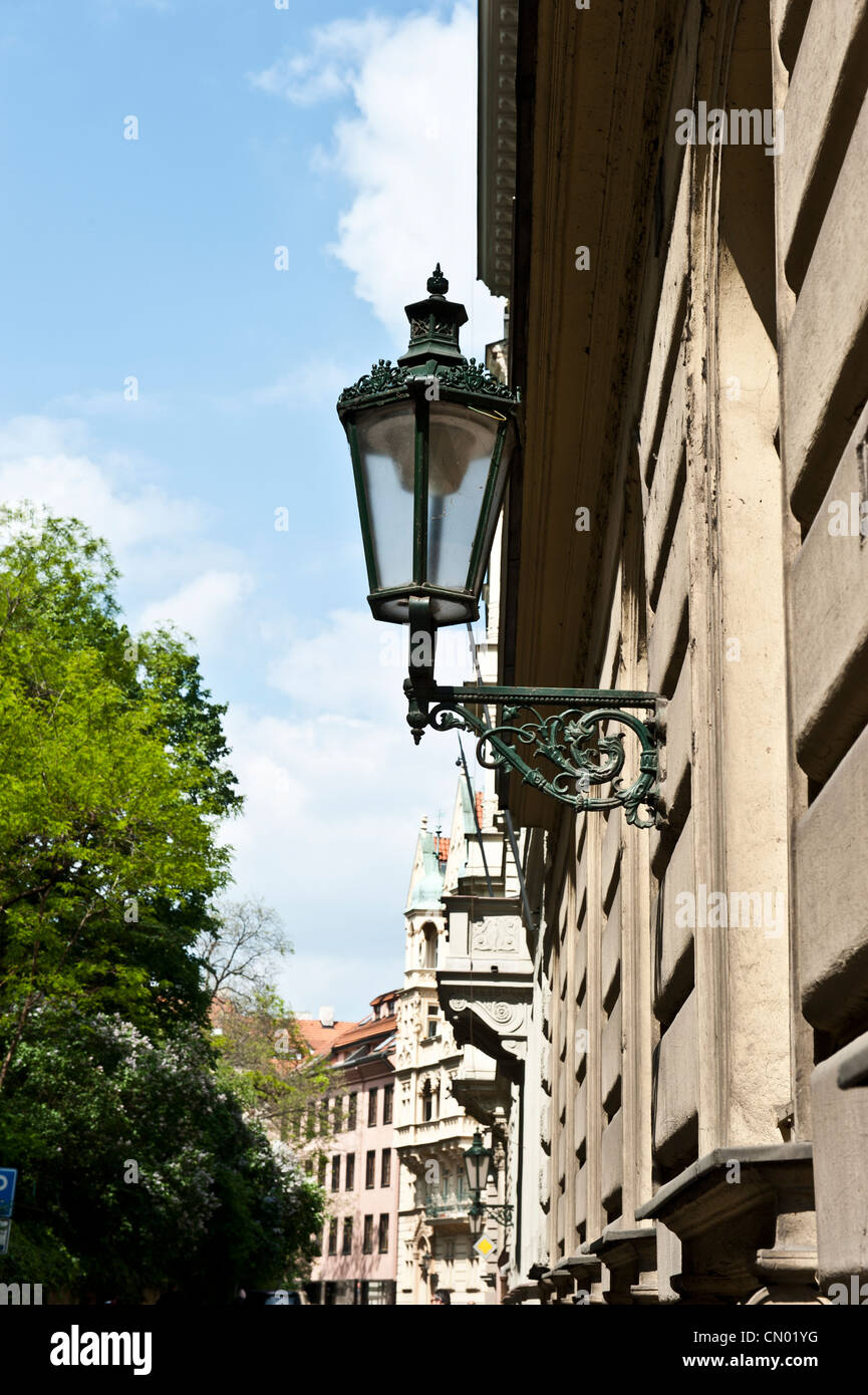 An unlit lamp post on the side of a building in the capital city of Prague, Czech Republic. - Stock Image