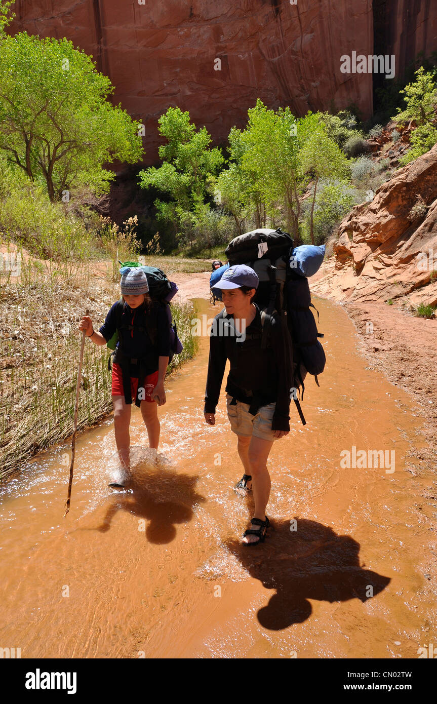 Mother and daughter backpacking in Coyote Gulch, a tributary of the Escalante River in Southern Utah. Stock Photo