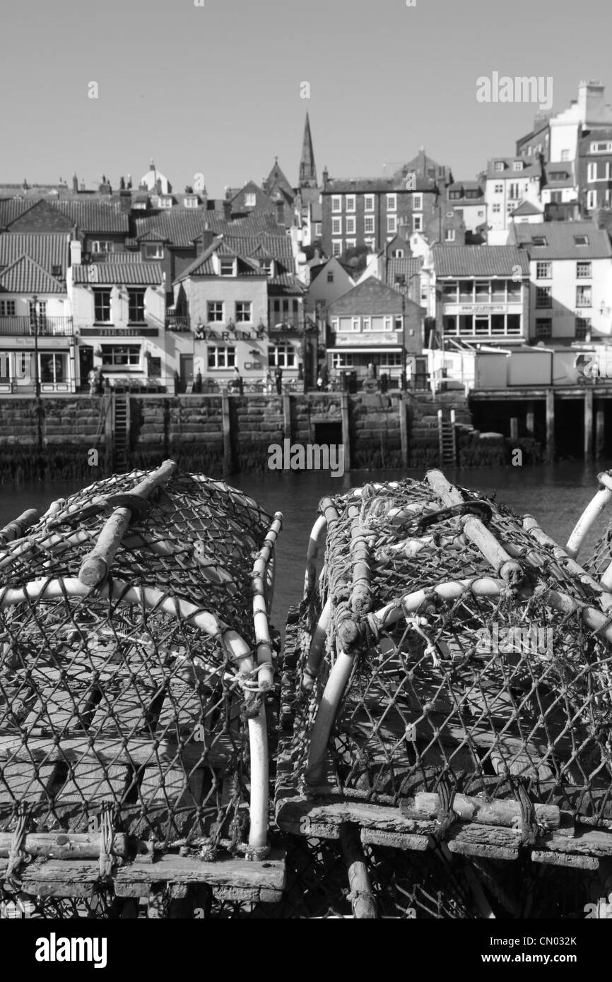 Black and white image of Whitby with empty Lobster pots in the foreground. - Stock Image