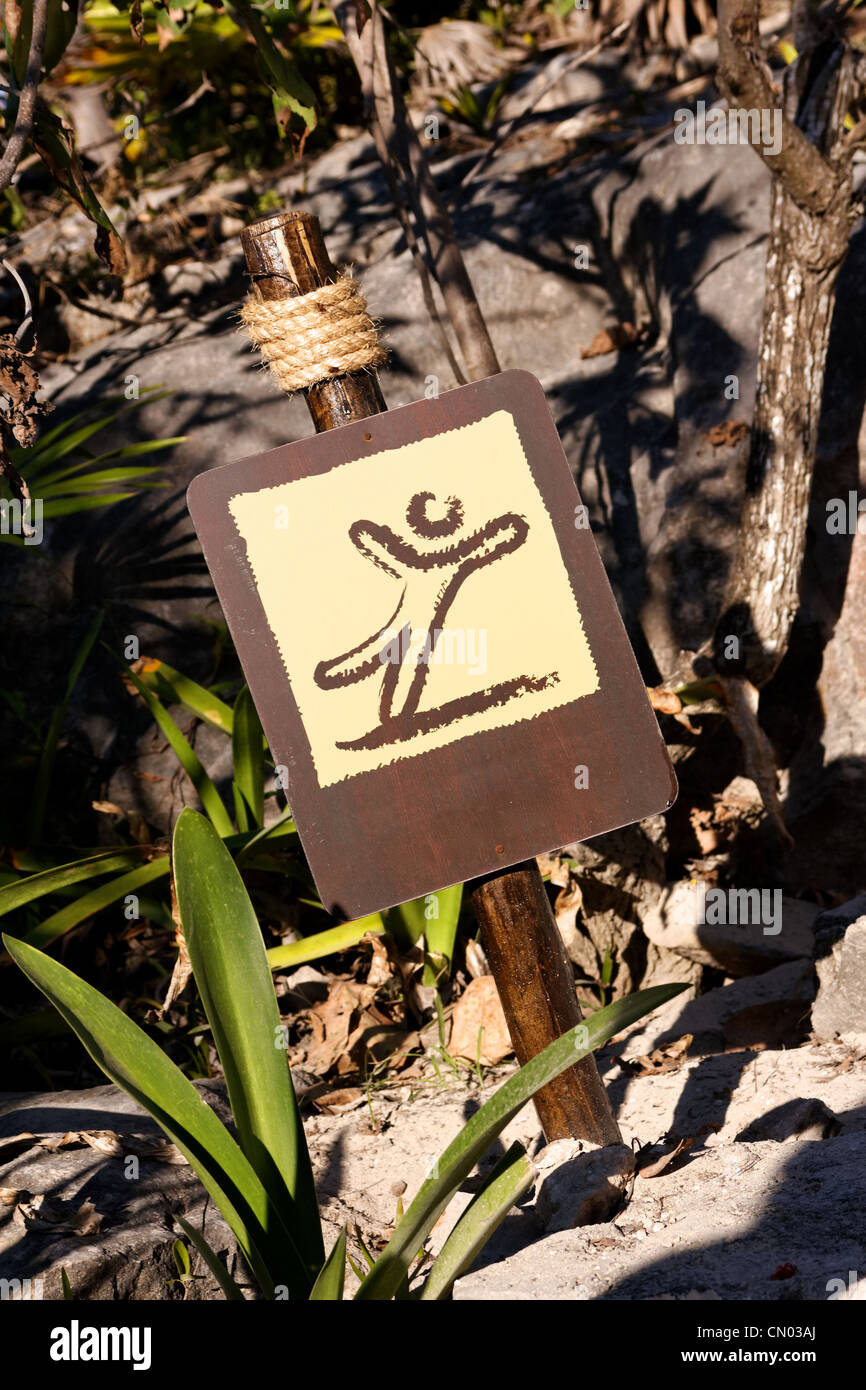 Caution slippery sign without text in tropical surroundings. - Stock Image