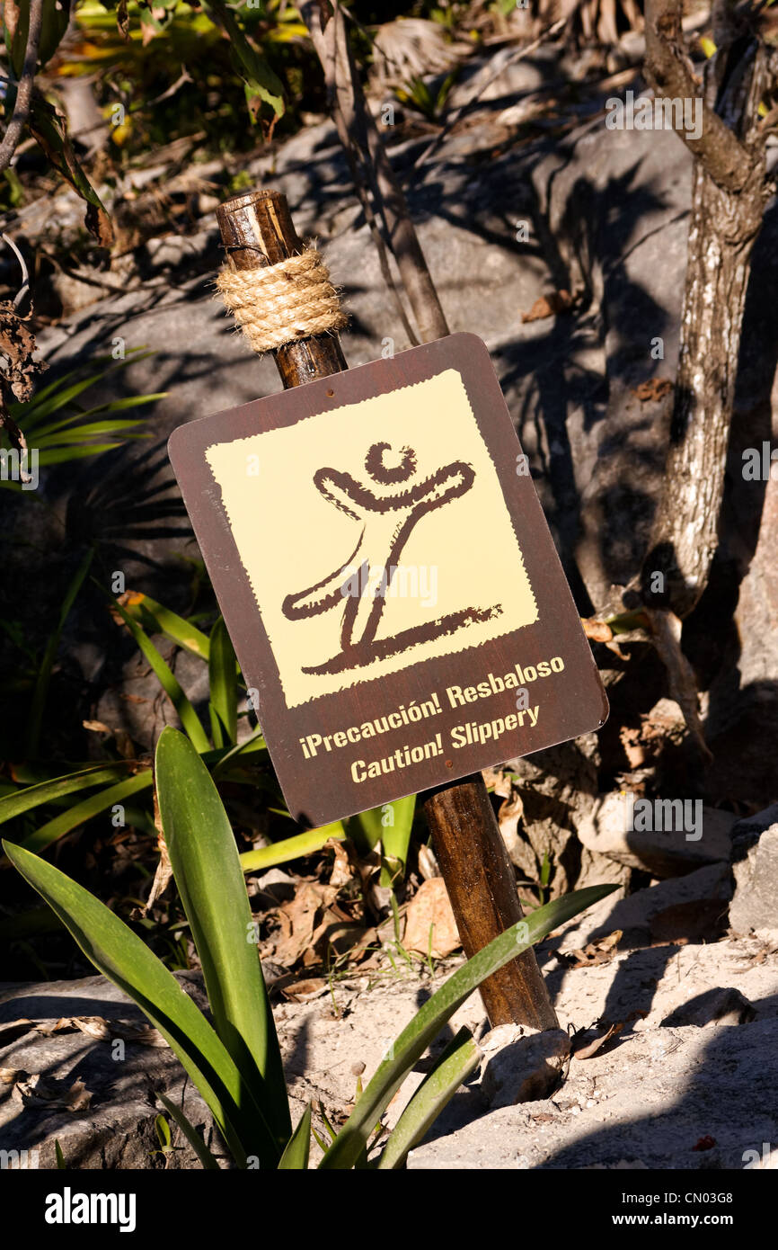 Bilingual sign in tropical surrounding warning of slippery ground, English (Caution Slippery) and Spanish (Precaucion - Stock Image