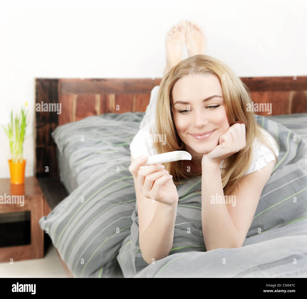 Happy woman holding pregnancy test, beautiful young female at home lying down in the bed, healthy lady checking - Stock Image