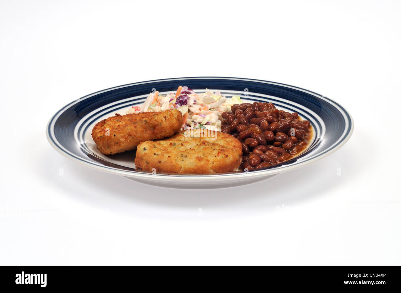 Plate of cod fishcakes with cole slaw and boston baked beans - Stock Image