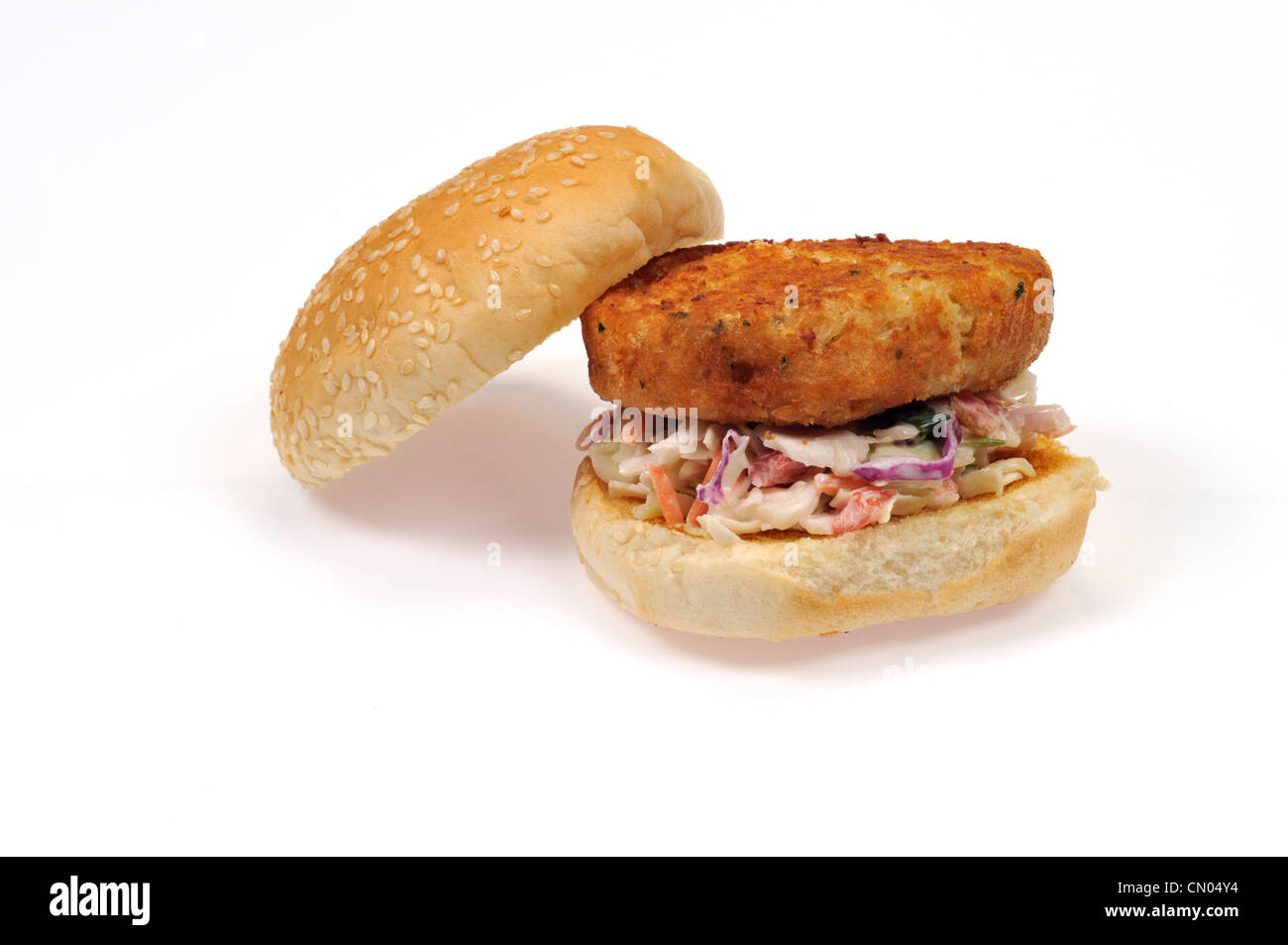Cod fish cake sandwich in a seeded roll on cole slaw - Stock Image