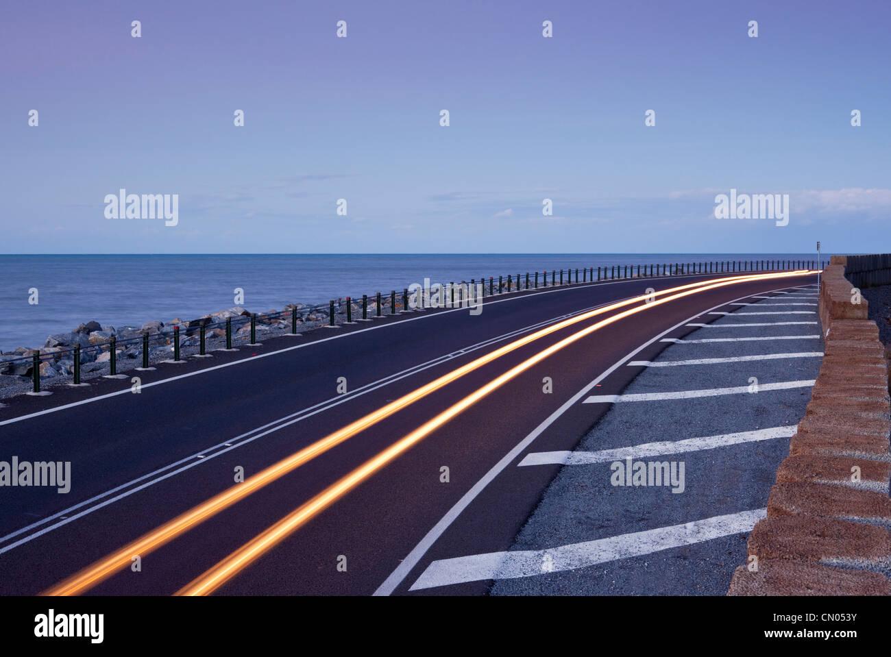 Car light trails on coastal highway.  Captain Cook Highway between Port Douglas and Cairns, Queensland, Australia - Stock Image