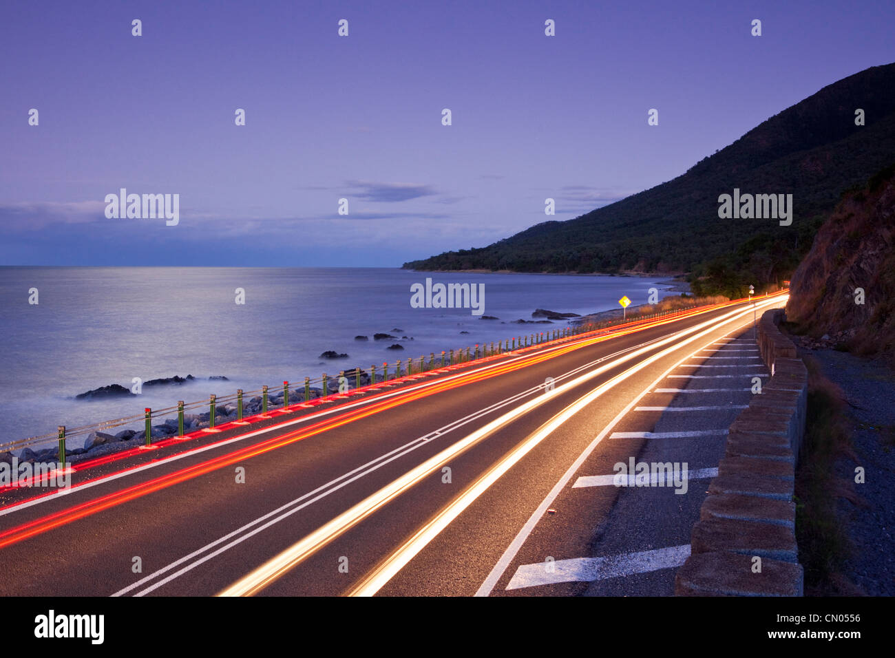 Car light trails on coastal highway.  Captain Cook Highway between Port Douglas and Cairns, Queensland, Australia - Stock Image