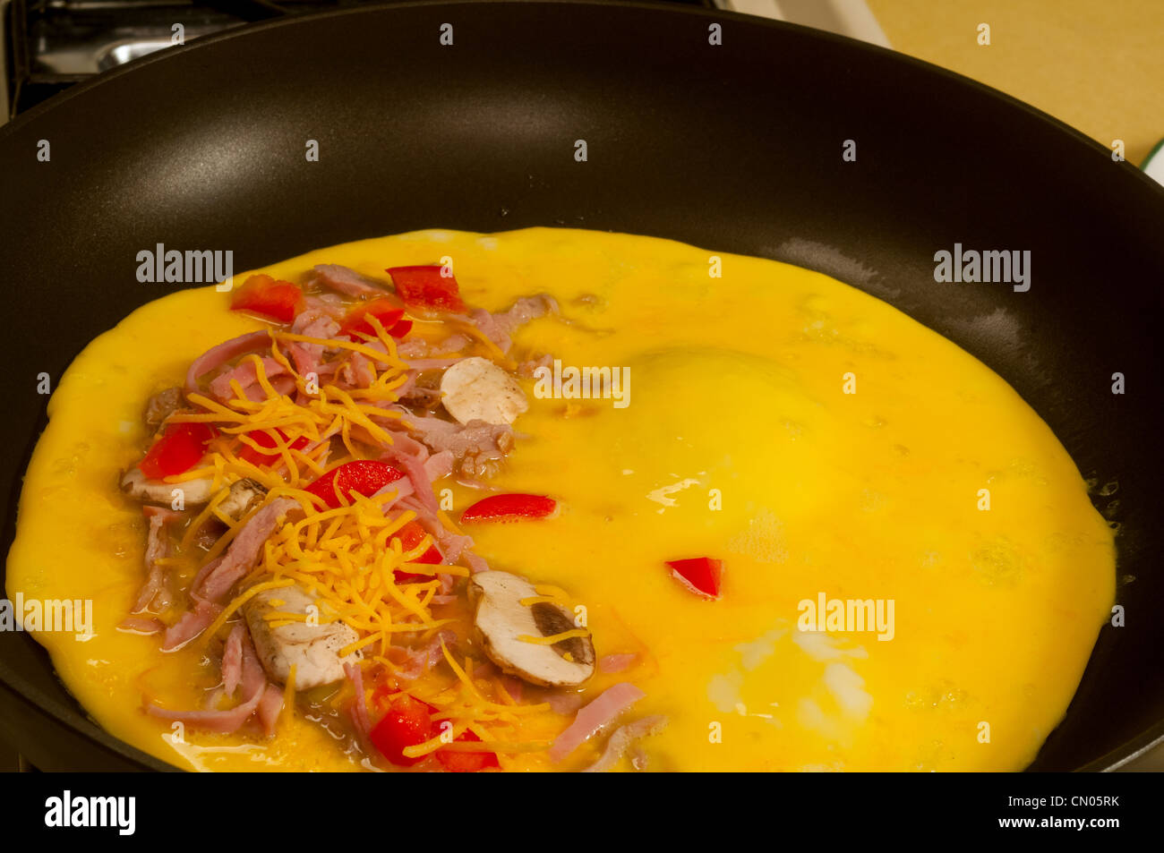 A three-egg omelet with meat, cheese, and mushrooms beginning to cook in a skillet - Stock Image