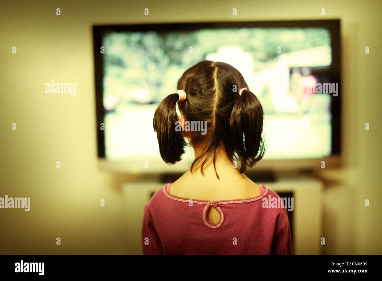 Girl watches tv screen. - Stock Image