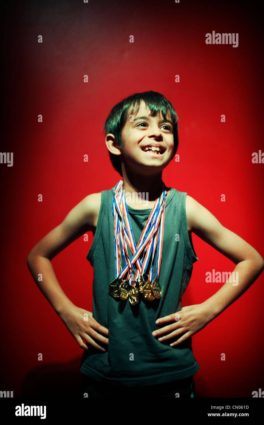 Winner. Boy strikes pose with plastic gold medals. - Stock Image