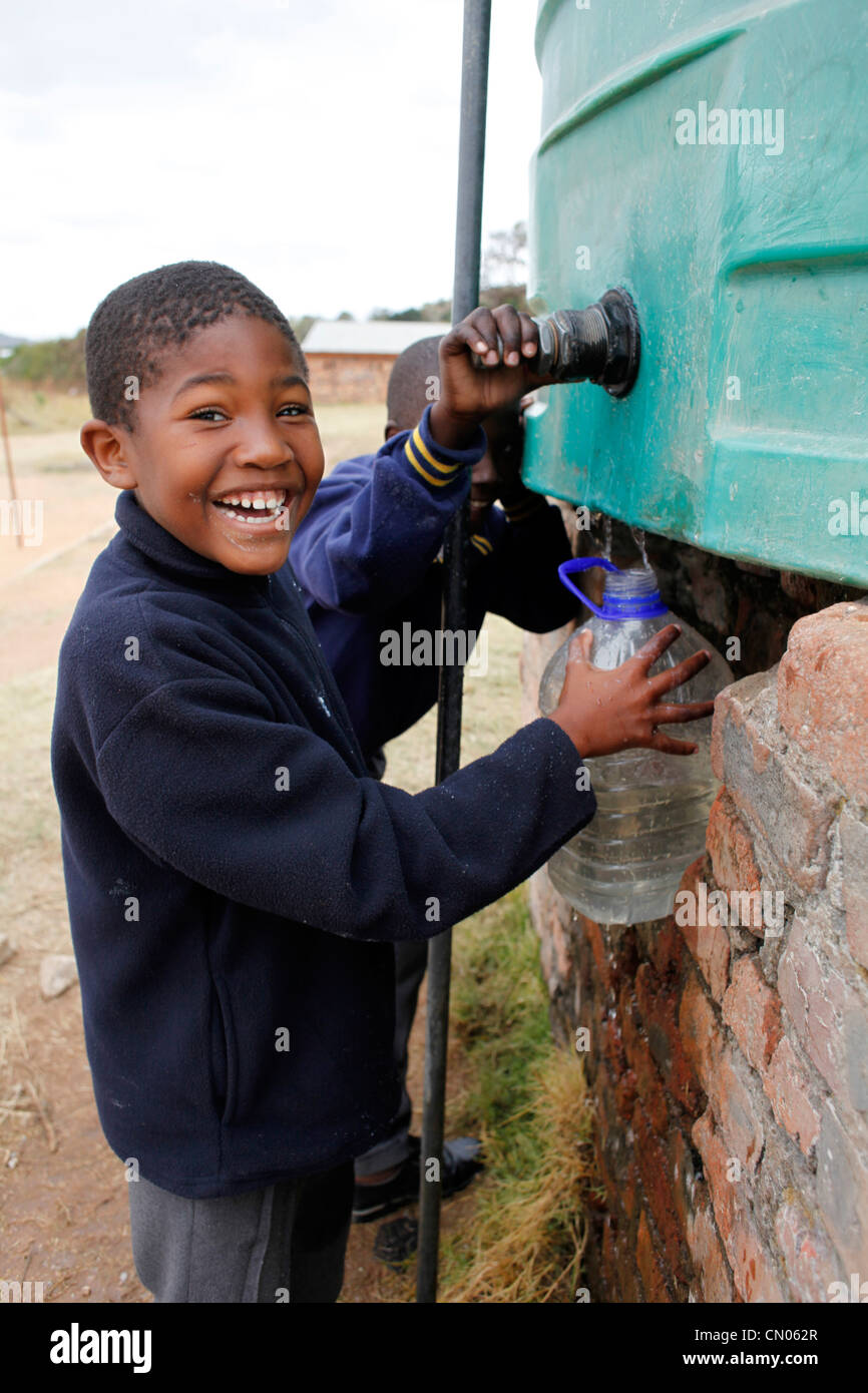 Students collect water for the classroom from a tank installed in their playground. Hlau Hlau, Mpumalanga, South - Stock Image