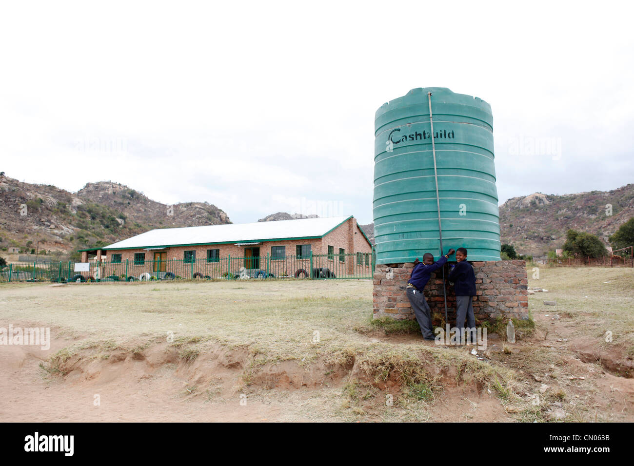 Students collect water from a tank installed in their school playground. Hlau Hlau, Mpumalanga, South Africa - Stock Image