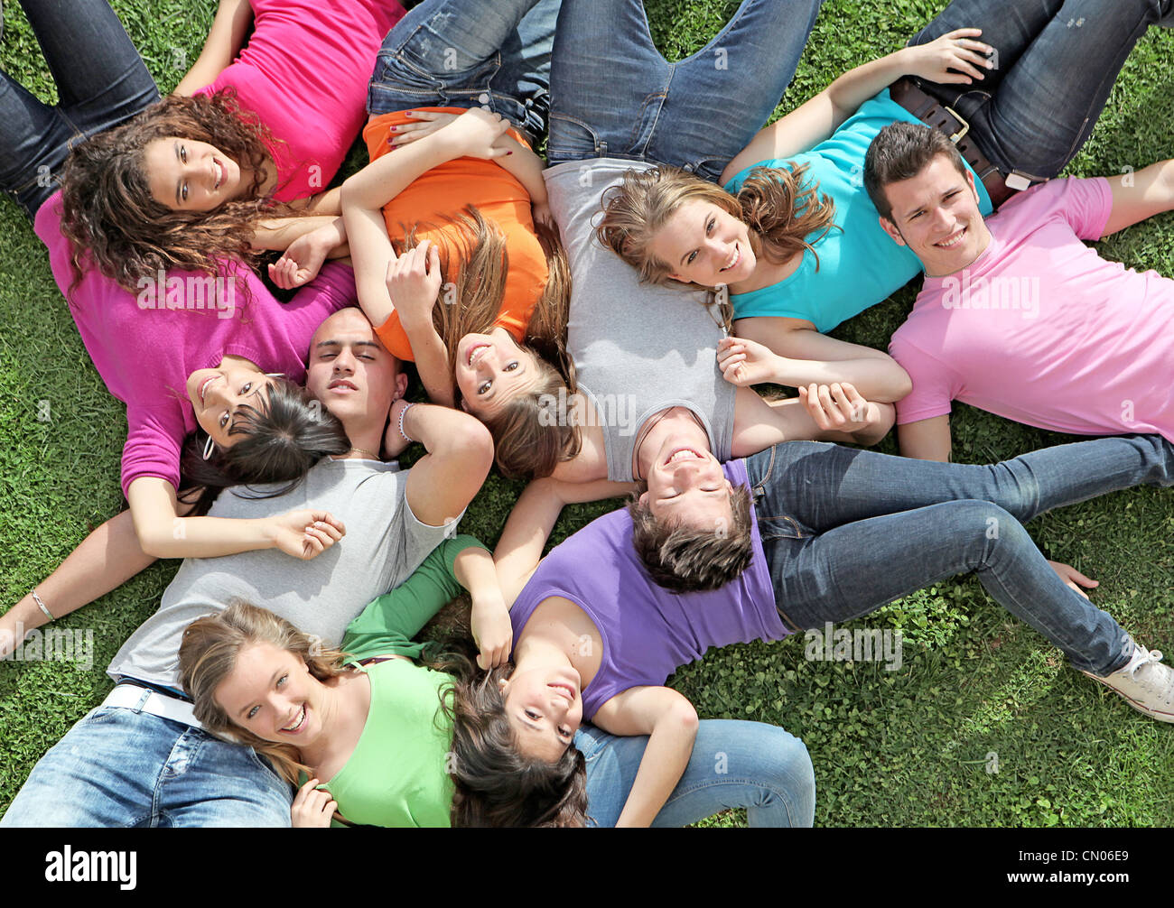 group of happy healthy kids laying outdoors on grass at summer camp - Stock Image