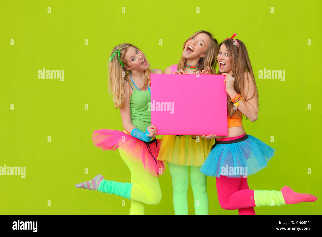 happy party teen girls in neon fancy dress clothing with blank board - Stock Image