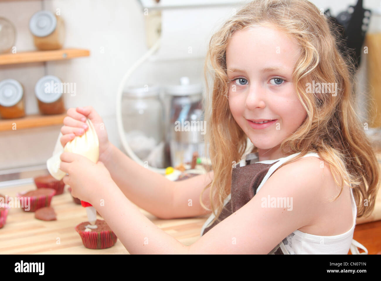 child cooking and helping decorate cupcakes - Stock Image