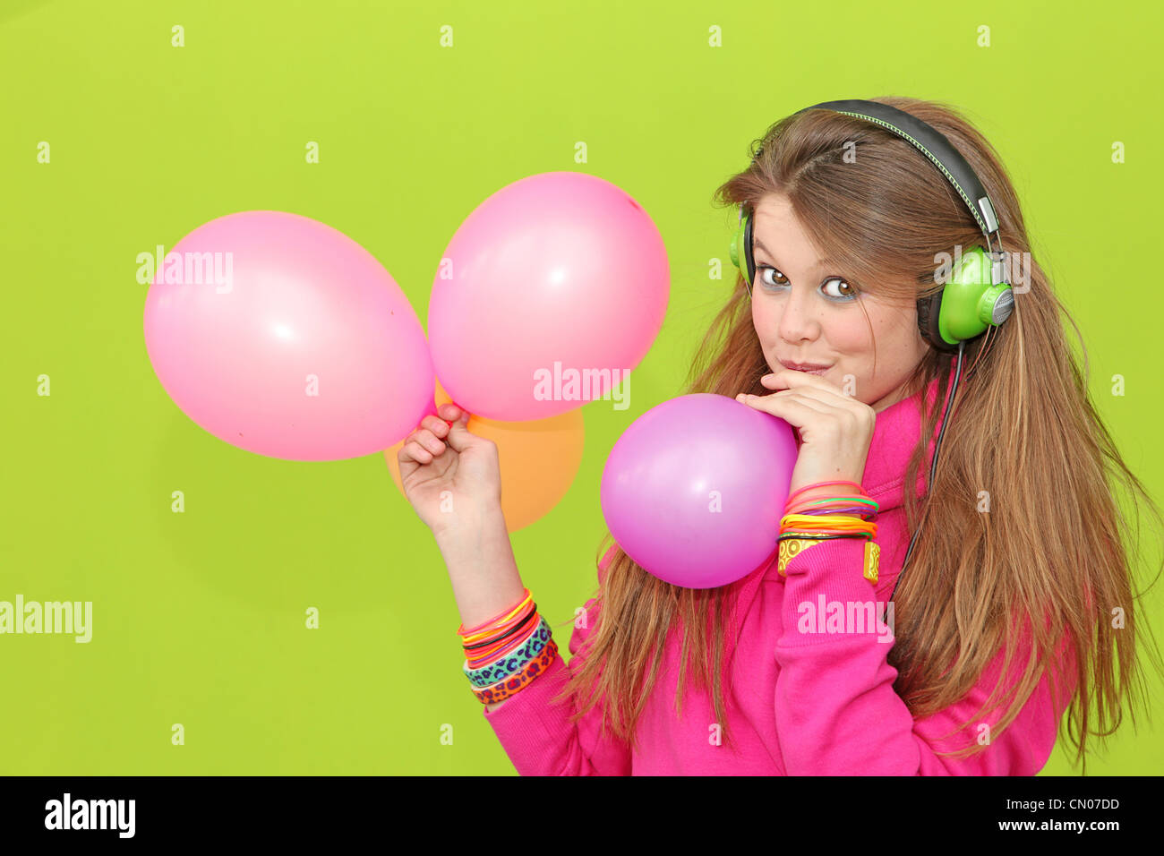 happy girl blowing up balloons at party - Stock Image